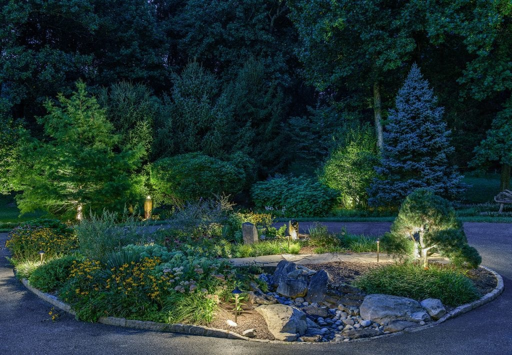 Round natural area with path in middle of circle driveway beautifully lit