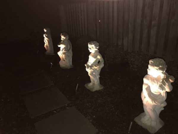4 cherub statues on side of McCauliffe property in Silver Spring, MD with uplights shining on them