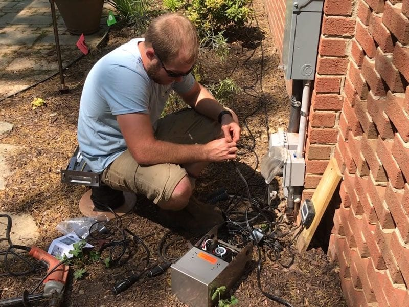 Landscape lighting expert working on a transformer