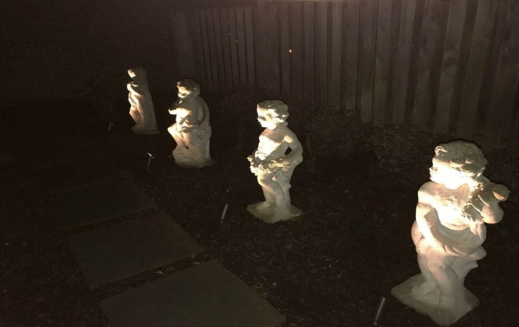 Uplights shining on a row of cherubic statues