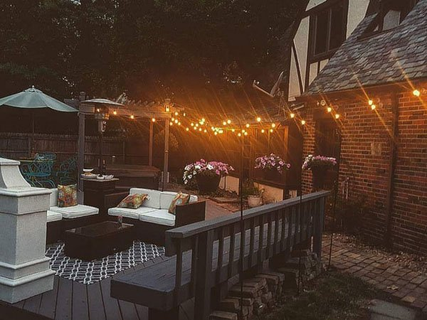String lights brightening an outdoor living space is a great benefit of landscape lighting